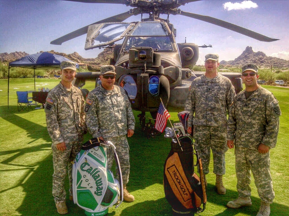 Four US soldiers stand in front of a helicopter on a golf courses